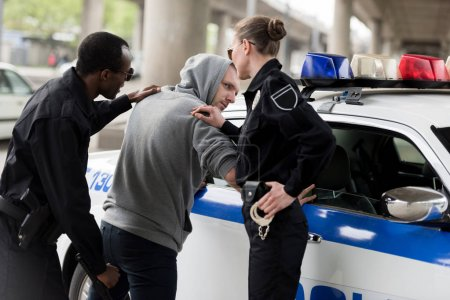 policeman and policewoman arresting young man in hoodie
