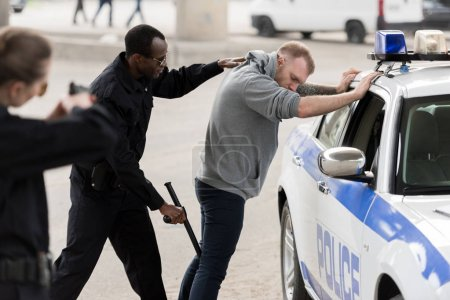 side view of african american arresting man while policewoman aiming at him by handgun