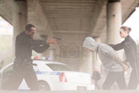 Photo pour Vue latérale du policier en colère visant arme de poing sur criminel masculin tout partenaire le tenant - image libre de droit