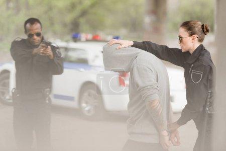 policewoman holding criminal while policeman aiming handgun at him