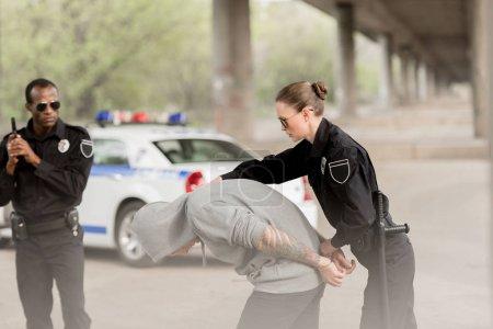 officers of police arresting male criminal in hoodie