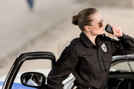 young policewoman in sunglasses talking on portable radio