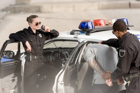 Photo for Young policewoman in sunglasses talking on radio set and policeman with arrested bandit - Royalty Free Image