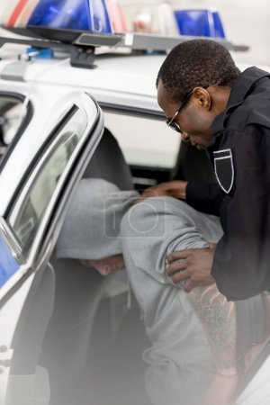 african american policeman placing male criminal in car