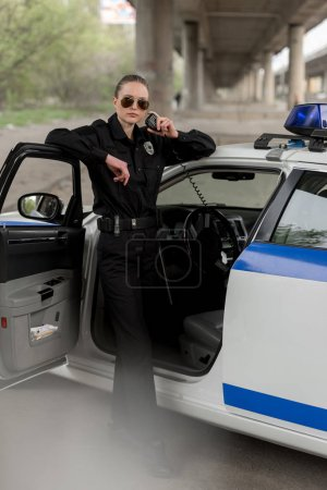 policewoman in sunglasses standing near car and talking on portable radio