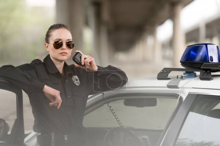 policewoman in sunglasses talking on portable radio near car