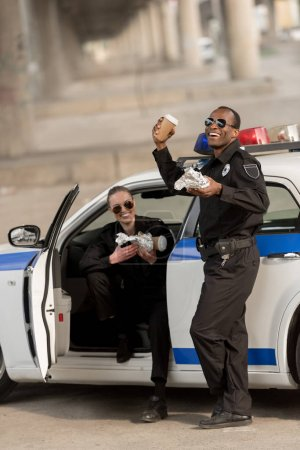 happy african american policeman with female partner having lunch
