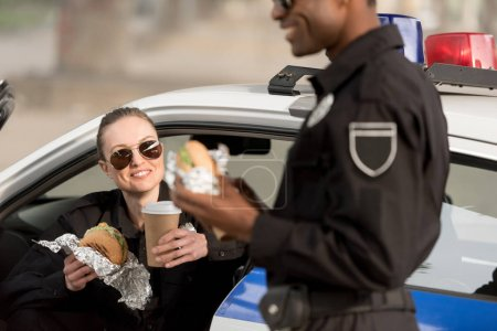 cropped shot of african american policeman having lunch with policewoman holding coffee cup