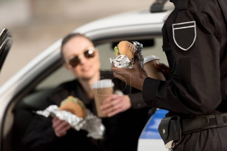 cropped image of policeman and policewoman with coffee cups and burgers