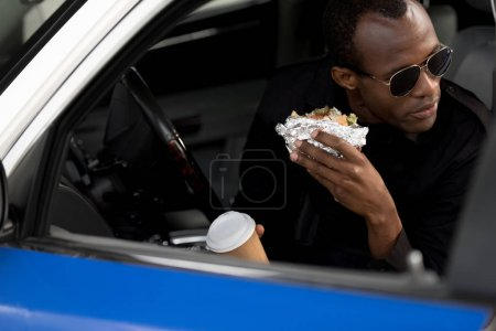 african american policeman in sunglasses having lunch in car