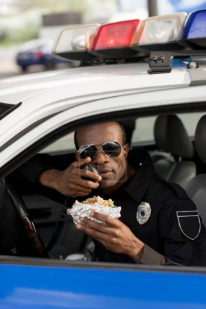 african american policeman holding burger and talking on portable radio in car