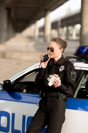 policewoman in sunglasses talking on portable radio and holding burger near car