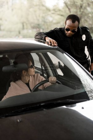 policeman in sunglasses talking to young woman sitting in car