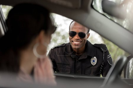 african american policeman in sunglasses smiling to young woman sitting in car