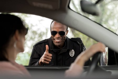 smiling african american policeman doing thumb up gesture to young woman sitting in car