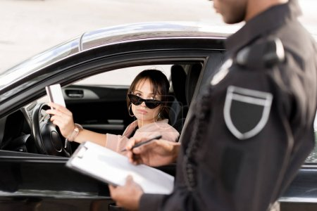 Cropped image of policeman with clipboard and pen talking to young driver in car giving driver license