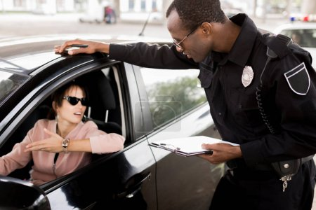 african american policeman with clipboard talking to young woman sitting in car