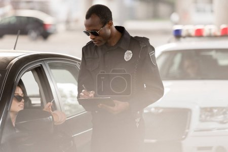 young woman in car giving driver license to african american policeman with clipboard and pen