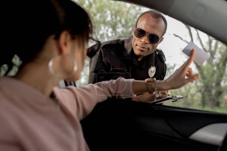 woman sitting in car and giving driver license to african american policeman