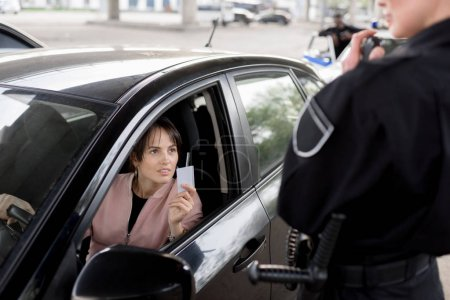 policewoman with portable radio and young woman in car holding driver license