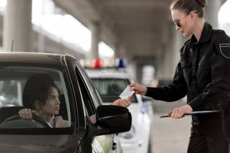 young woman in car giving driver license to policewoman in sunglasses