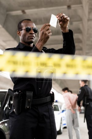 policeman in sunglasses holding plastic zipper with drugs while his partner arresting female criminal