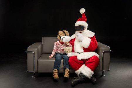 Photo for Santa Claus with child eating popcorn and wearing virtual reality headsets - Royalty Free Image
