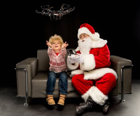 Photo for Santa Claus with child using hexacopter drone and sitting on sofa - Royalty Free Image