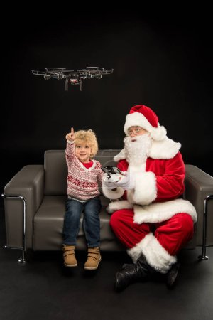 Photo for Santa Claus using hexacopter drone with child on black - Royalty Free Image