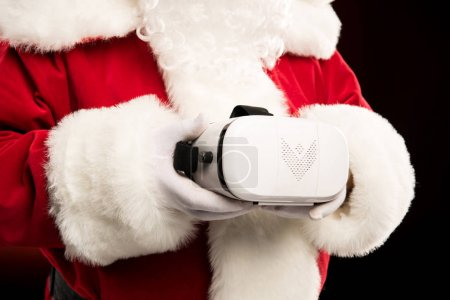 Photo for Cropped shot of Santa Claus holding virtual reality headset in hands - Royalty Free Image