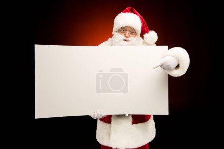 Photo for Santa Claus pointing on blank card on dark - Royalty Free Image