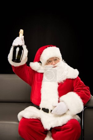 Santa Claus holding bottle of champagne