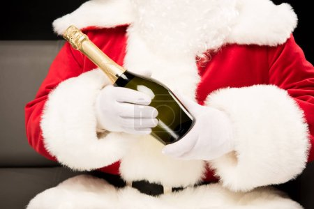 Photo for Cropped shot of Santa Claus holding bottle of champagne in hands - Royalty Free Image