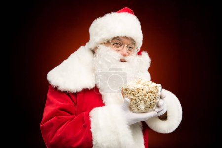 Photo for Portrait of Santa Claus showing full bowl of popcorn on dark - Royalty Free Image