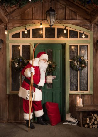 Photo for Santa Claus standing with skis and knocking in door - Royalty Free Image