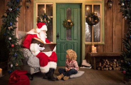 Photo pour Livre de lecture du Père Noël au petit enfant pendant la période de Noël - image libre de droit