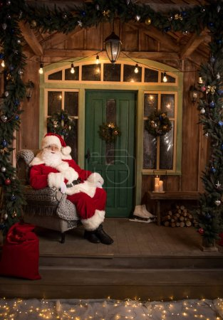 Photo for Happy Santa Claus sitting in grey armchair and looking at camera - Royalty Free Image