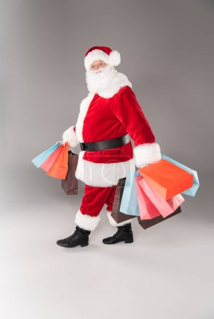 Photo for Happy Santa Claus walking with a pile of shopping bags on grey - Royalty Free Image