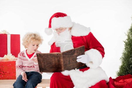 Photo for Santa Claus and kid sitting and reading a book together near gift boxes - Royalty Free Image