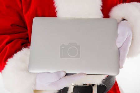 Santa Claus hand showing laptop