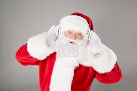 Photo for Happy Santa Claus listening music with headphones and posing - Royalty Free Image