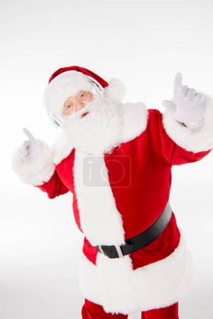 Photo for Happy Santa Claus listening music with headphones and dancing - Royalty Free Image