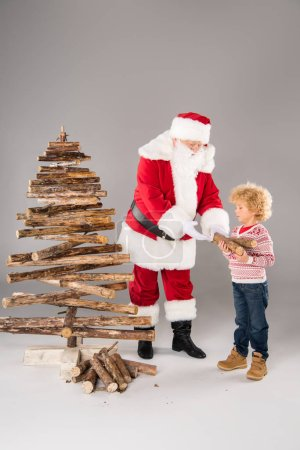 Photo for Santa Claus with kid creating Christmas tree from firewood on grey - Royalty Free Image