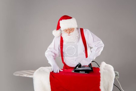 Photo for Santa Claus ironing his coat on ironing board - Royalty Free Image