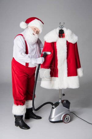 Photo for Santa Claus cleaning his coat with vacuum cleaner - Royalty Free Image