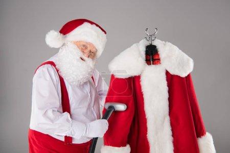 Photo pour Santa Claus nettoyage son manteau avec aspirateur - image libre de droit