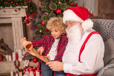 Photo for Happy Santa Claus and child on his knee reading Christmas wishlist - Royalty Free Image