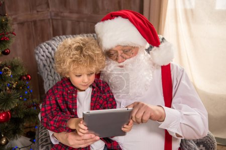 Santa Claus with kid on knee using tablet