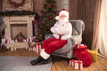 Photo for Happy Santa Claus sitting in grey armchair with arms crossed and looking at camera - Royalty Free Image