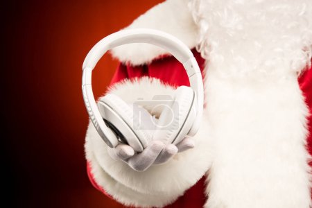 Photo for Cropped image of Santa Claus hand showing headphones - Royalty Free Image